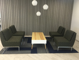 Collaborative space featuring seating, table, and lighting